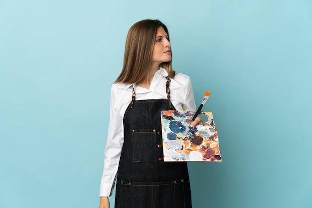 Młody artysta słowacka kobieta na białym tle na niebieskiej ścianie, patrząc z boku