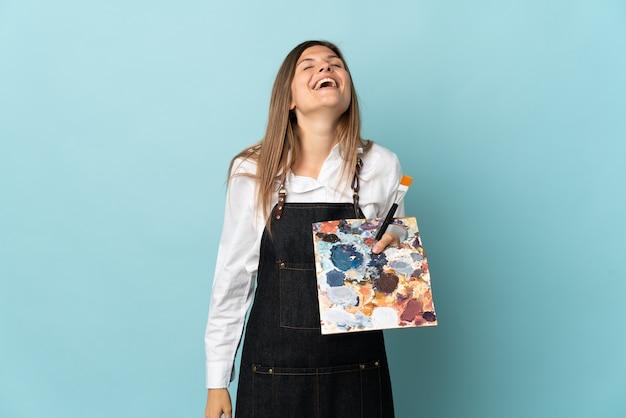 Młody artysta słowacka kobieta na białym tle na niebieskiej ścianie, śmiejąc się
