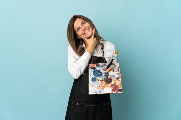 Młody artysta słowacka kobieta na białym tle na niebieskiej ścianie szczęśliwa i uśmiechnięta