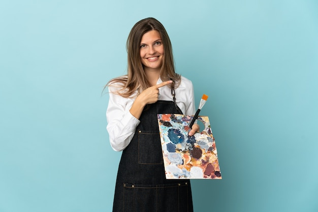Młody artysta słowacka kobieta na białym tle na niebieskiej ścianie, wskazując w bok, aby zaprezentować produkt
