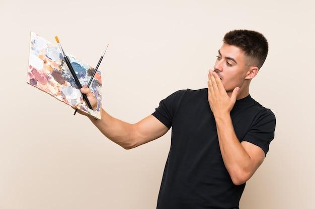 Młody artysta z zaskoczeniem i zszokowanym wyrazem twarzy