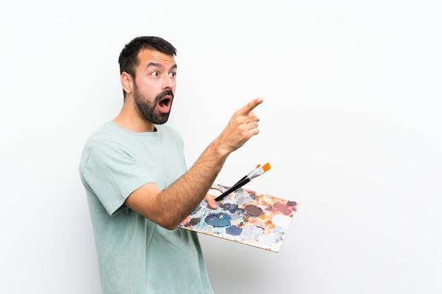 Młody artysty mężczyzna trzyma paletę nad odosobnioną ścianą wskazuje daleko od