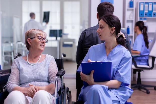 Młody asystent sprawdzający formularz rejestracyjny niepełnosprawnego starszego pacjenta siedzącego na wózku inwalidzkim w szpitalnej poczekalni