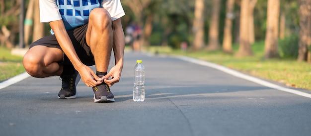 Młody atleta mężczyzna wiąże działających buty w parku plenerowym.