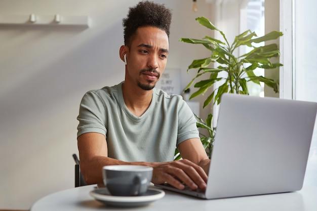 Młody atrakcyjny african american zamyślony chłopiec siedzi przy stole w kawiarni, pracuje na laptopie, patrzy na monitor