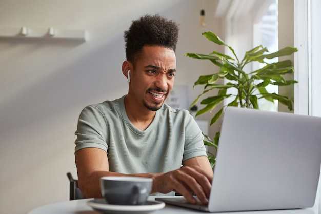 Młody atrakcyjny afroamerykanin siedzi przy stoliku w kawiarni, pracuje przy laptopie, patrzy na monitor z niesmakiem, coś nie tak z jego ulubioną stroną.
