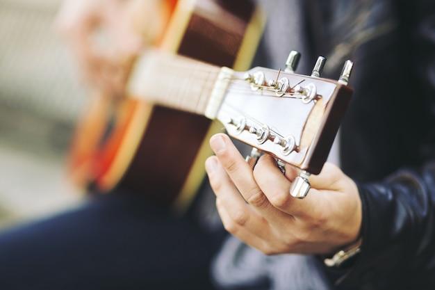 Młody atrakcyjny artysta uliczny z gitarą