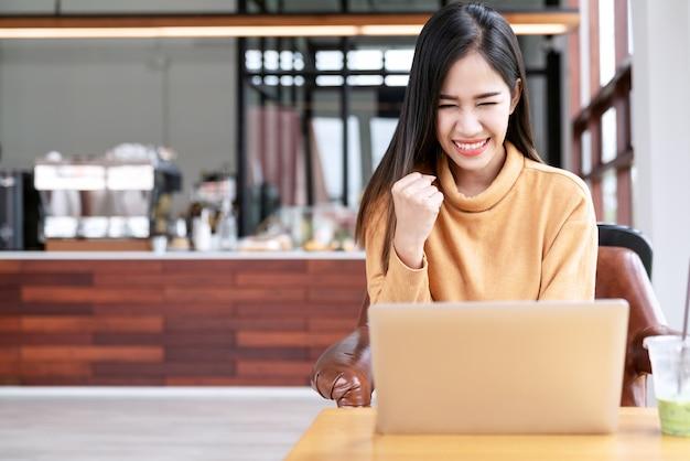 Młody atrakcyjny azjatykci żeński uczeń używa laptop oblicza