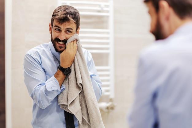 Młody atrakcyjny biznesmen brodaty przygotowuje się do pracy. jest w łazience i wyciera twarz ręcznikiem.