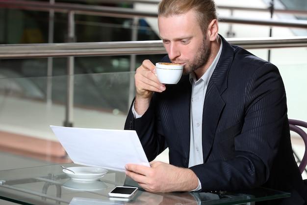 Młody atrakcyjny biznesmen obiad i pracy w kawiarni