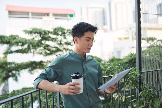 Młody atrakcyjny biznesmen posiadający dokumenty, papiery