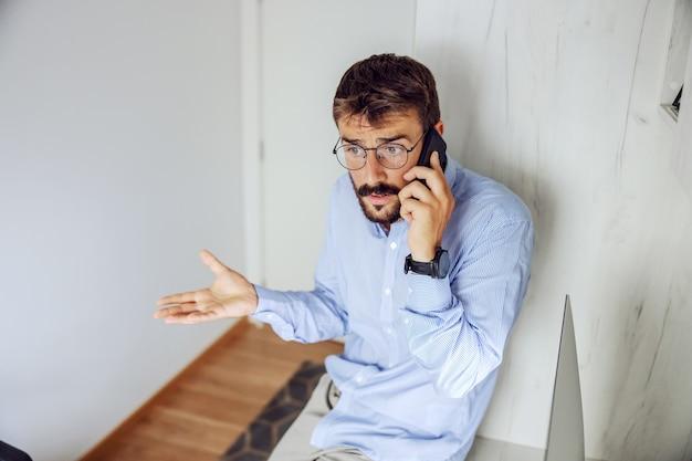 Młody atrakcyjny biznesmen poważny siedzi na biurku w swoim biurze i mając ważne wezwanie tworzą jego szefa.