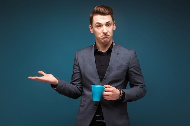 Młody atrakcyjny biznesmen w szarej kurtce i czarnej koszuli trzymać niebieski kubek