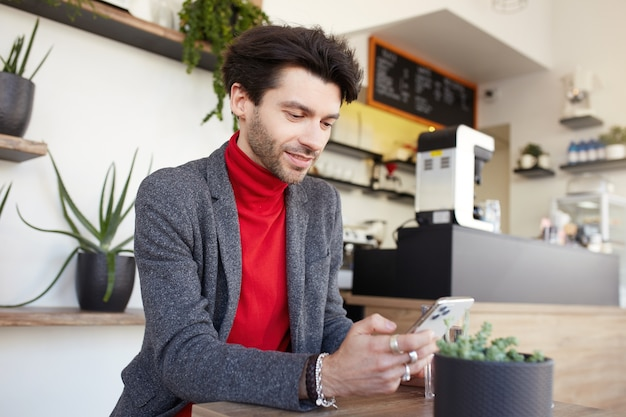 Młody atrakcyjny brązowowłosy nieogolony mężczyzna siedzi w miejskiej kawiarni