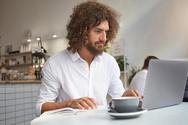 Młody atrakcyjny brodaty biznesmen pracuje poza biurem ze swoimi notatkami roboczymi i nowoczesnym laptopem, korzystając z publicznego wi-fi w kawiarni, skoncentrowany na swojej pracy