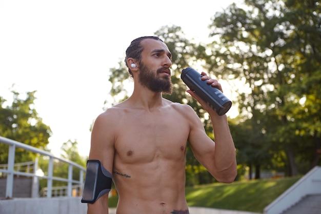 Młody atrakcyjny brodaty facet uprawia sporty ekstremalne w parku, pije wodę, prowadzi zdrowy, aktywny tryb życia. męski model fitness.