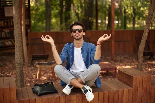 Młody atrakcyjny brodaty mężczyzna siedzi w parku miejskim ze skrzyżowanymi nogami, podnosząc ręce gestem mudry, będąc spokojnym podczas medytacji, nosząc zwykłe ubrania