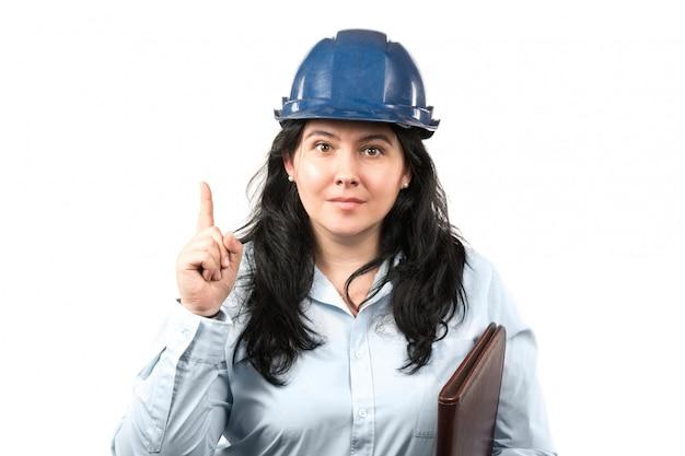 Młody atrakcyjny brunetki kobiety inżynier lub architekt z błękitnym zbawczym kapeluszem pokazuje pointeru palec odizolowywającego na białym tle