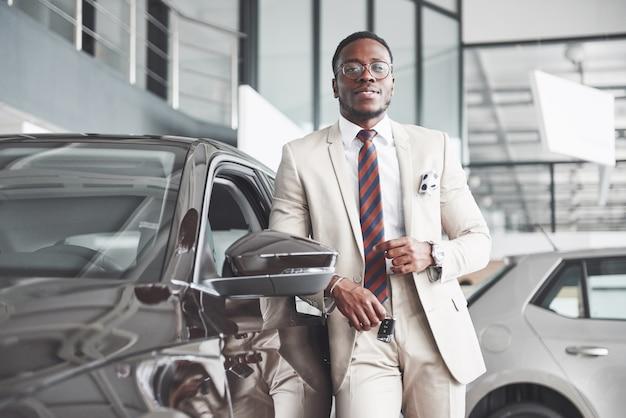 Młody atrakcyjny czarny biznesmen kupuje nowy samochód, marzenia się spełniają
