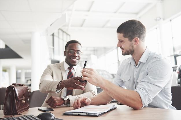 Młody atrakcyjny czarny biznesmen kupuje nowy samochód, podpisuje umowę i zabiera klucze do kierownika.