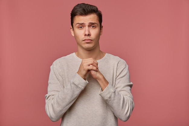 Młody atrakcyjny facet ubrany w czysty długi rękaw, składa życzenie, liczy na szczęście na egzaminach i skrzyżowane dłonie, prosi, by nie wystawiać mu złej oceny, stoi na różowym tle.