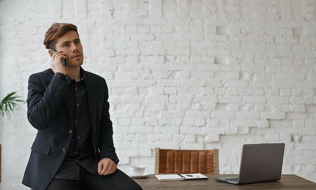 Młody atrakcyjny inżynier ma poważny telefon w biurze na poddaszu