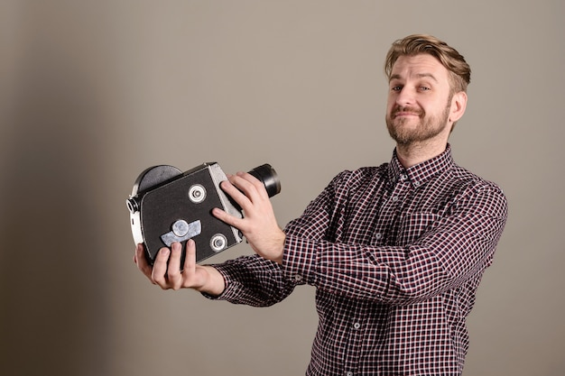Młody atrakcyjny kamerzysta w kraciastej koszuli idzie do starej kamery filmowej