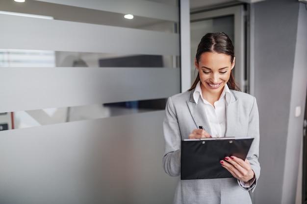 Młody atrakcyjny kaukaski pracownik płci żeńskiej w garniturze stojącej w hali firmy i pisania zadań schowka na ten dzień.