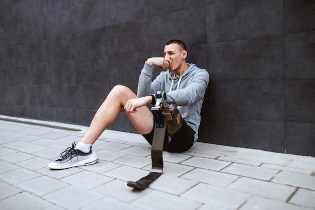 Młody atrakcyjny kaukaski sportowiec ze sztuczną nogą siedzi na ziemi, opierając się o ścianę i jedząc świeże jabłko.