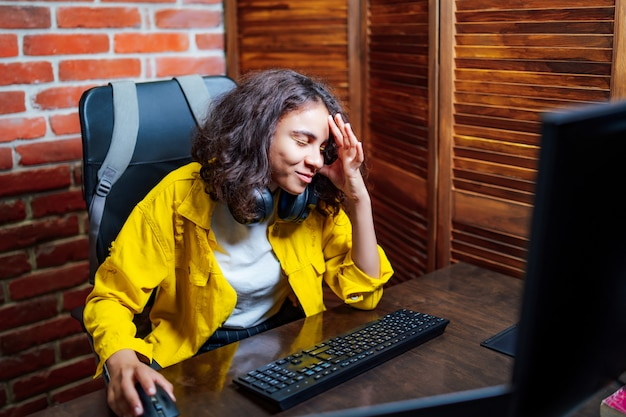 Młody atrakcyjny kobiety obsiadanie przed otwartym laptopem.