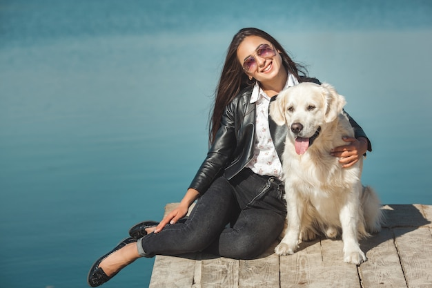 Młody atrakcyjny kobiety obsiadanie przy molem z jej psem. najlepsi przyjaciele na zewnątrz