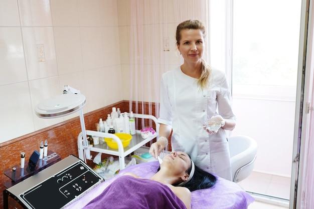 Młody atrakcyjny kosmetolog w gabinecie kosmetycznym ze sprzętem medycznym. kosmetolog dermatolog w klinice.