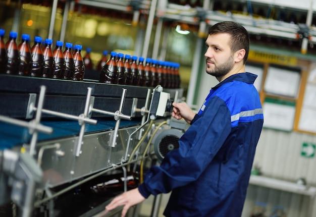 Młody atrakcyjny męski browar lub pracownik browaru w mundurze na tle przenośnika taśmowego z plastikowymi butelkami piwa