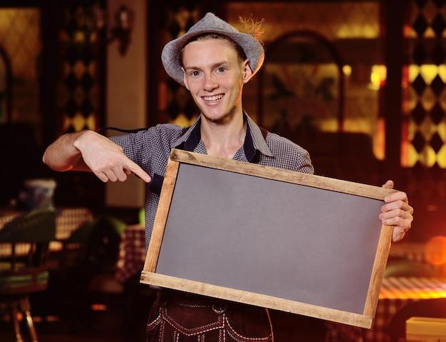 Młody atrakcyjny męski kelner w bawarskim stroju i w kapeluszu z piórkiem trzymającym tablicę