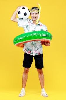 Młody atrakcyjny mężczyzna azji w białej koszuli hawajskiej na sobie żółtą maskę do nurkowania i zielony pierścień pływacki wokół jego talii trzymając piłkę na żółtym tle. koncepcja na wakacje na plaży.