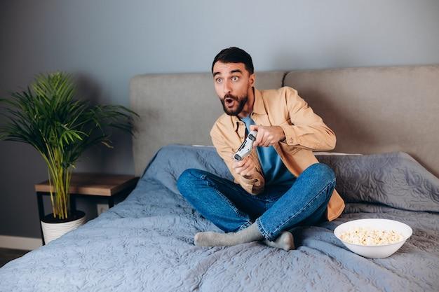 Młody atrakcyjny mężczyzna gra konsolowa gra przed kamerą, pokonując swojego przeciwnika online. biały człowiek na kanapie z pop kukurydzą. koncepcja zawodów e-sportowych.