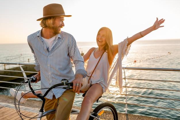Młody atrakcyjny mężczyzna i kobieta podróżująca na rowerach, romantyczna para na wakacjach nad morzem o zachodzie słońca, strój w stylu boho hipster, przyjaciele dobrze się bawią