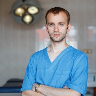 Młody atrakcyjny mężczyzna lekarz w niebieskiej odzieży medycznej stoi w szpitalu na sali operacyjnej