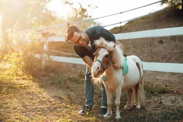 Młody atrakcyjny mężczyzna lekarz weterynarii badanie i karmienie adorable little pony konia.