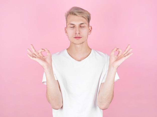 Młody atrakcyjny mężczyzna medytuje w pozycji lotosu na różowym tle.
