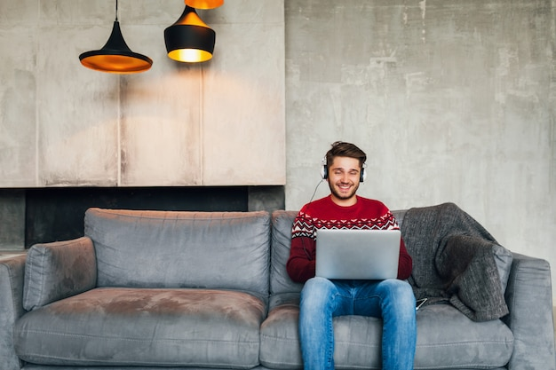 Młody atrakcyjny mężczyzna na kanapie w domu zimą w słuchawkach, słuchanie muzyki, ubrany w czerwony sweter z dzianiny, pracujący na laptopie, freelancer, uśmiechnięty, szczęśliwy, pozytywny