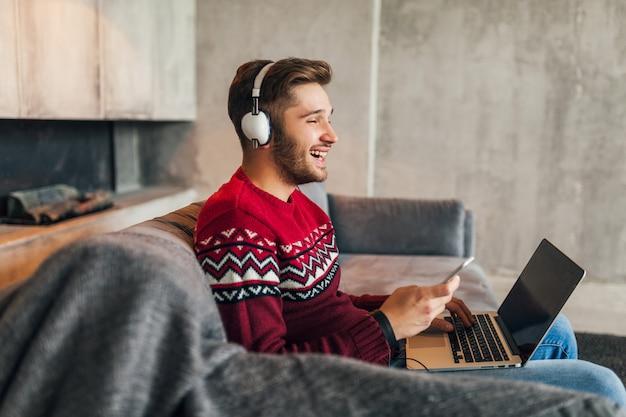 Młody atrakcyjny mężczyzna na kanapie w domu zimą ze smartfonem w słuchawkach, słuchanie muzyki, ubrany w czerwony sweter z dzianiny, pracujący na laptopie, freelancer, uśmiechnięty, szczęśliwy, pozytywny