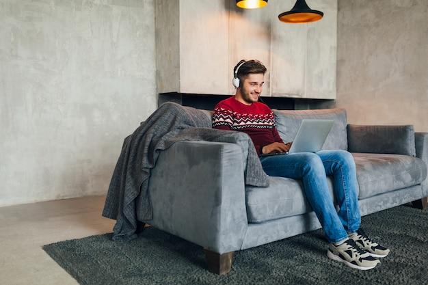 Młody atrakcyjny mężczyzna na kanapie w domu zimą ze smartfonem w słuchawkach, słuchanie muzyki, ubrany w czerwony sweter z dzianiny, pracujący na laptopie, freelancer