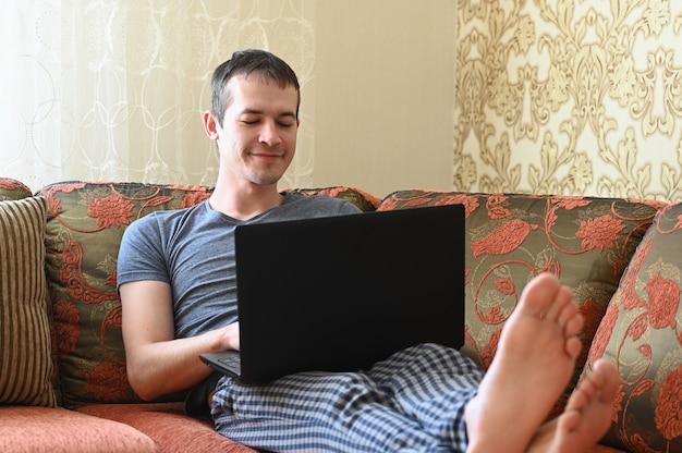Młody atrakcyjny mężczyzna pracuje z domowego żywego pokoju obsiadania na kanapie z laptopem. koncepcja pracy zdalnej