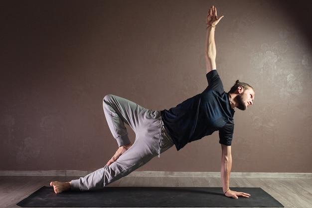Młody atrakcyjny mężczyzna praktykuje jogę na sobie odzież sportową
