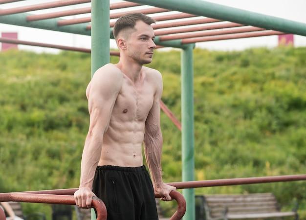 Młody atrakcyjny mężczyzna rasy kaukaskiej robi pompki na barach. koncepcja treningu