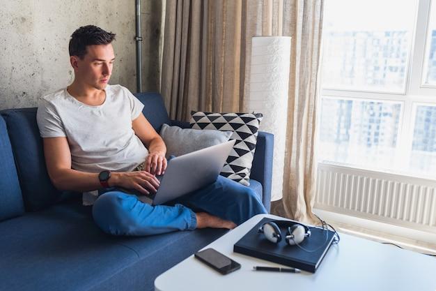Młody atrakcyjny mężczyzna siedzi na kanapie w domu, pracując na komputerze przenośnym w trybie online, za pomocą internetu