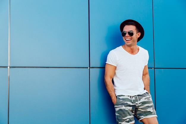 Młody atrakcyjny mężczyzna stoi na błękitnym ściennym tle w okularach przeciwsłonecznych