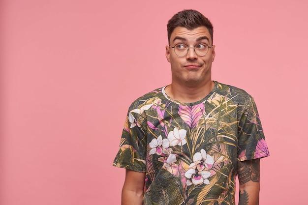 Młody atrakcyjny mężczyzna stojący przed kamerą na różowym tle z uniesionymi brwiami, odwracający wzrok, w okularach i drukowanej koszulce, wydaje się znudzony i obojętny