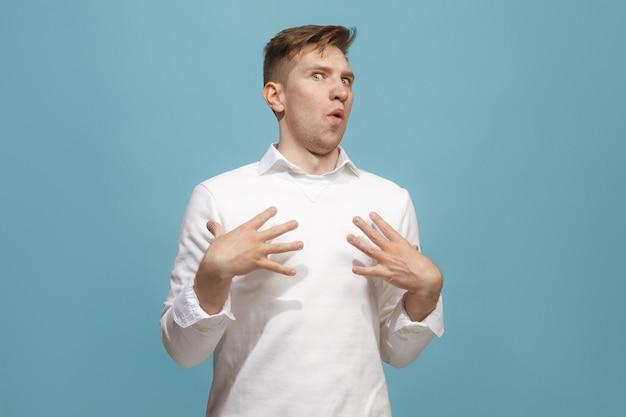 Młody atrakcyjny mężczyzna szuka zaskoczony na białym tle na niebiesko